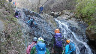 ロープで確保しながら横向きの滝を慎重に越える